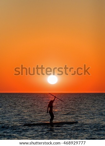 The silhouette of a young woman on a paddle board at sunrise.