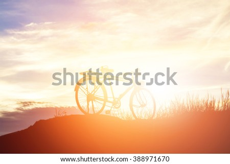 The silhouette of  bicycle on the hill with beautiful sunrise background