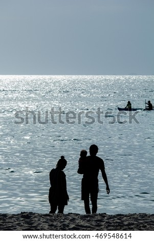 The silhouette of family on the beach at the sunset time with reflection of the sunlight on the water , dark tone photo
