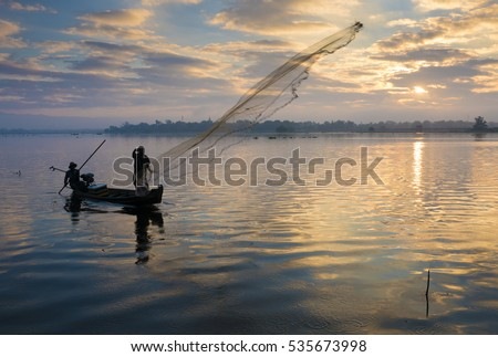 The silhouette of Fisherman throwing net in the early morning near U Bein Bridge, sunrise, Taungthaman Lake near Amarapura, Myanmar