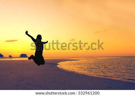 The silhouette of jumping human with sea beach background and orange background - stock photo