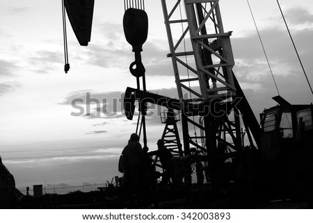 The silhouette of oil pump in the work, in the evening