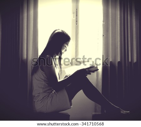 The silhouette of stressed and depressed woman reading book and worried about her studies with the black vignette on the corner and cream tone light on the center - stock photo