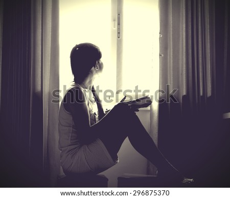 The silhouette of stressed and depressed woman worried about her studies - stock photo