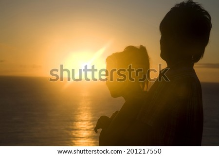 The silhouette of the man hugging from the behind of the woman at dusk - stock photo