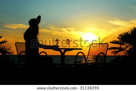 The silhouette of the woman sits at a table in cafe on a sundown