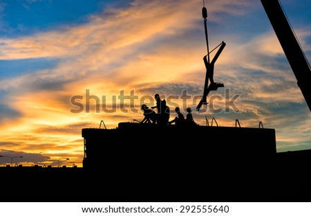 The silhouette of workers Construction Site - stock photo