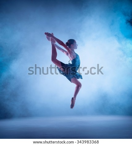 The silhouette of young ballerina jumping on a blue  smoke background. - stock photo