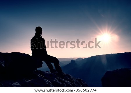 The silhouette of young hiker sitting on the rock and enjoying view into morning misty rocky mountains.