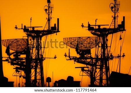 The silhouettes of naval ships taken at sunset - stock photo