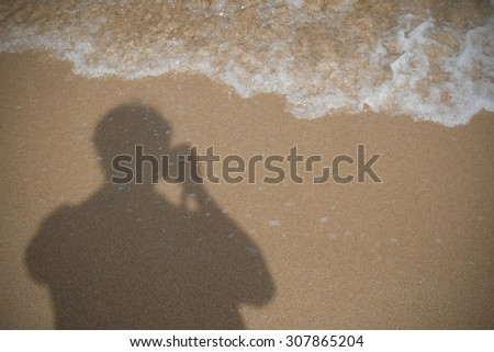 The silhouettes of photographer on the beach in late afternoon sunlight - stock photo