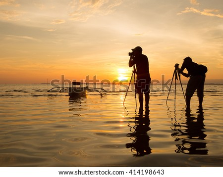 The sillhouette of photographer taking photo on sunrise.