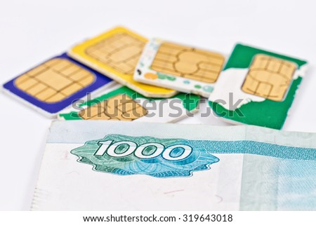 The simcards of different mobile service providers are together with the banknote 1000 rubles - stock photo