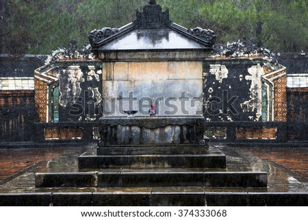 The simple, undecorated, tomb of Emperor Tu Duc, Vietnam, with an incense offering.  On a wet  misty day, in the rain. - stock photo