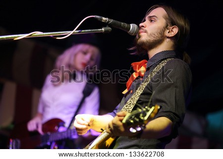 The singer with a guitar and a red ribbon performing on stage. - stock photo