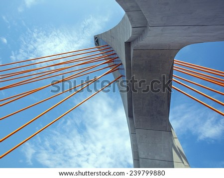 The single tower of a cable stayed bridge with orange steel cables  - stock photo