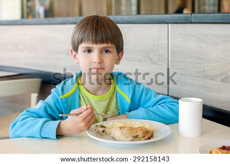 The six years boy eats chicken with mashed potatoes