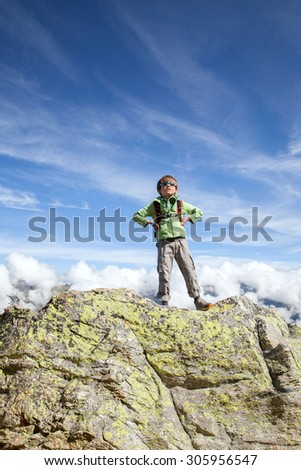 The six years boy stands on top of big rock in mountains