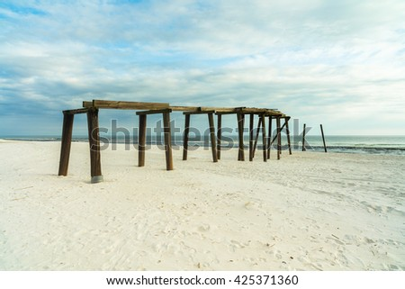The skeletal remains of an old wooden pier on a Florida panhandle beach in the late afternoon. - stock photo