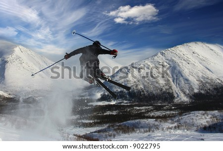 The skier in mountains in flight from a back has jumped from a springboard