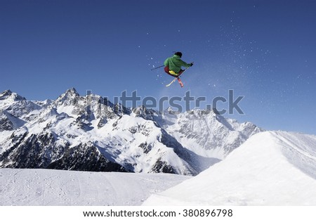 The skier makes a jump in the winter in the mountains