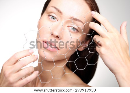 The skin cells.Portrait of a beautiful woman stretching before him with a wire mesh of hexagonal windows, a symbol of the construction of skin cells