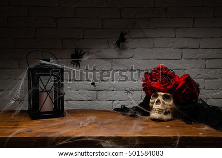 The skull and candle on a wooden table, spiders, spider web background brick wall, halloween, santa muerte
