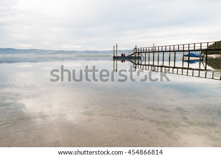 The sky at dusk reflecting the jetty and clouds in the calm waters of a lagoon in Kynsna, South Africa - stock photo