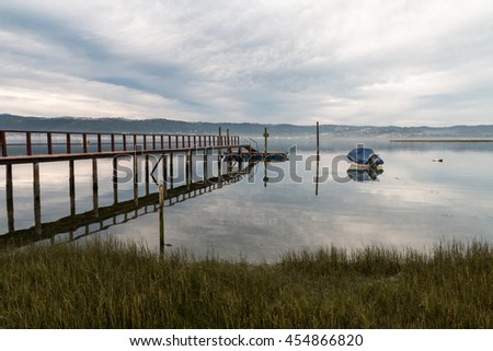 The sky at dusk reflecting the jetty, motor boat and clouds in the calm waters of a lagoon in Kynsna, South Africa - stock photo
