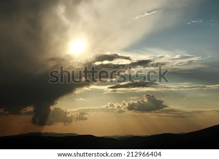 The sky in the rays of the sun at sunset in mountains, nature background - stock photo
