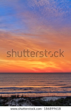 The sky over Florida's Atlantic Ocean coast is painted with vivid colors by the rising sun as waves break beyond the dunes. - stock photo