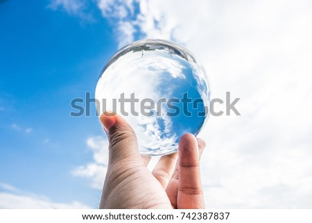 The sky reflected in the crystal ball,environment saving, abstract meaning environment in your hand.
