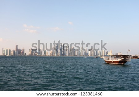 The skyline of Doha, Qatar, in the last days of December 2012, with a dhow in the foreground. - stock photo