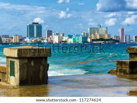 The skyline of Havana with a turbulent sea and El Malecon in the foreground - stock photo