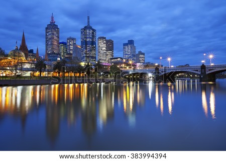 The skyline of Melbourne, Australia with Flinders Street Station and the Princes Bridge from across the Yarra River at night. - stock photo