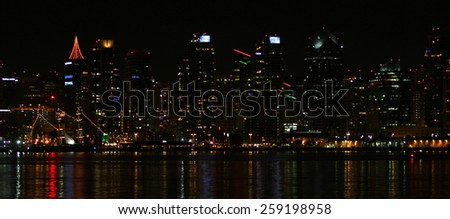 The skyline of San Diego at night with reflection in the water. - stock photo