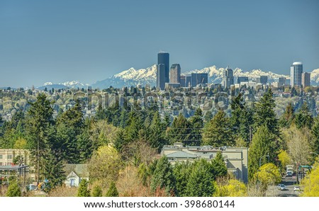 The Skyline of Seattle, Washington Looms Large over the Surrounding Greenery as the Olympic Mountains Stand Guard