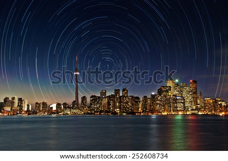 The skyline of Toronto lights up at night as the star rotate around the structures. This is a composite image of stars to the North. buildings are not in focus