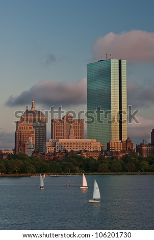 The skyscrapers of Boston's Copley square stand out at sunset while sailboats fill the Charles River - stock photo