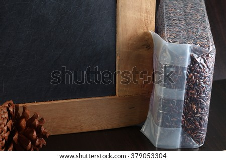 The slate board and rice berry put on dark color wooden background represent the raw food material concept related idea.