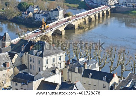 The slate roofs of the medieval town of Chinon and the bridge over the River Vienne in France - stock photo
