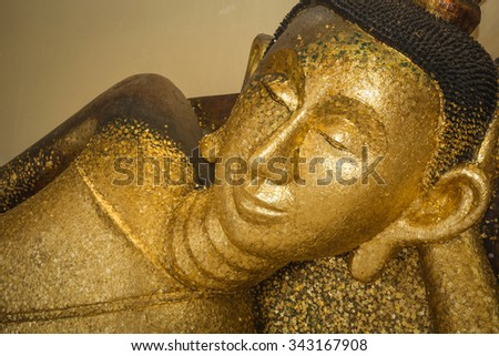 The sleeping Buddha The front has a gold Buddhist lead off the face and body. - stock photo