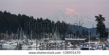The sleepy harbor of the town of Gig Harbor with Mt Rainier catching the light from sunset in the background - stock photo