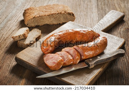 the sliced tasty sausage with bread on the wooden table - stock photo