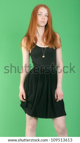 the slim girl with red hair on a green background