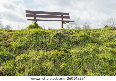 The slope of the deck is covered with grass and on top of the dike is an empty wooden bench. It is a cloudy day at the end of the winter season. - stock photo