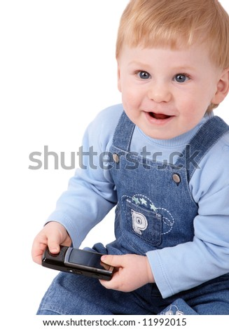 The small beautiful boy laughs and sits at a mobile phone in hands
