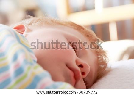 The small beautiful boy sleeps a head on a pillow - stock photo