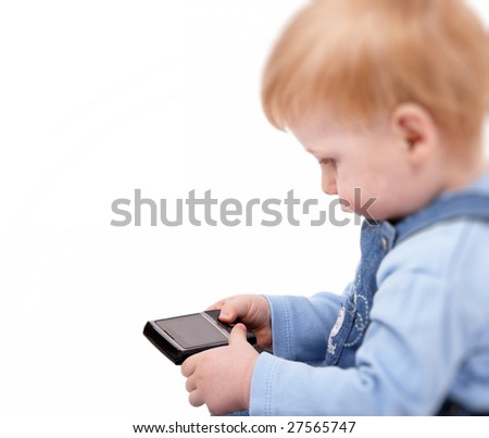 The small beautiful boy with curiosity examines a mobile phone
