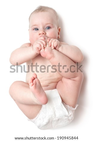 the small beautiful caucasian child lies on back and licks a foot. isolated on white  - stock photo